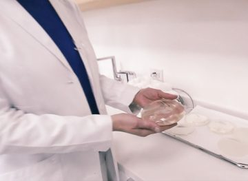 Doctor holding breast implant and discussing breast implant illness